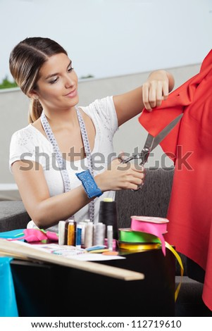Young female fashion designer cutting a red fabric with dressmaking accessories on table