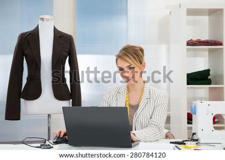 Young Female Fashion Designer Using Laptop In Studio - stock photo