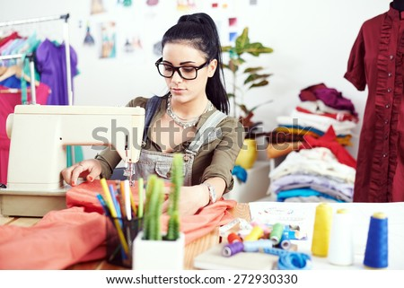 Young female fashion designer working on sewing machine - stock photo