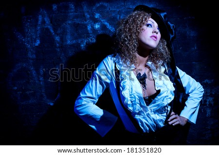 Young female fashion model against wall in the dark
