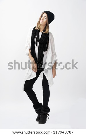young female fashion model wearing black tights white top and black winter hat