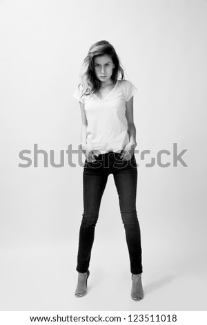 young female fashion model with blond hair wearing jeans and t-shirt - stock photo