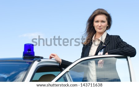 Young female FBI agent standing near car open door - stock photo