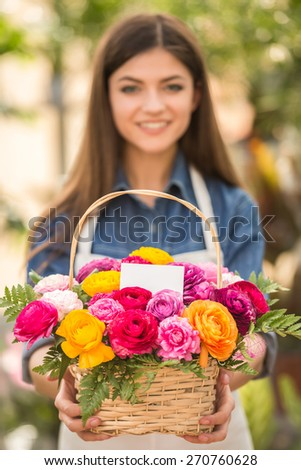 Young female florist holding bouquet of flowers in shop. Focus on bouquet. - stock photo