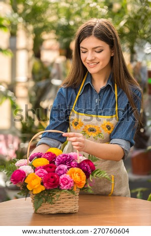 Young female florist making bouquet of flowers in shop. - stock photo