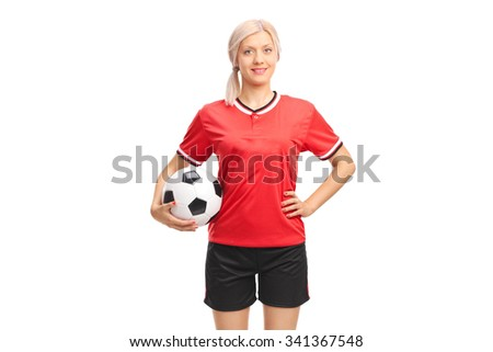 Young female football player in a red jersey holding a football and looking at the camera isolated on white background - stock photo