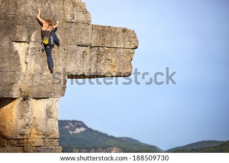 Young female free climber on a cliff  - stock photo