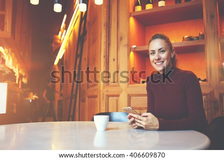 Young female freelancer with beautiful smile is sitting with smart phone in modern co-working space interior,gorgeous cheerful woman waiting for a call on her cell telephone during rest in coffee shop - stock photo