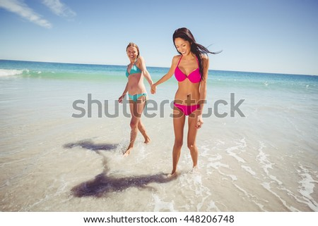 Young female friends holding hands and walking on beach