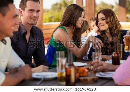 Young female friends talking to each other while hanging out with a bunch of friends at a restaurant