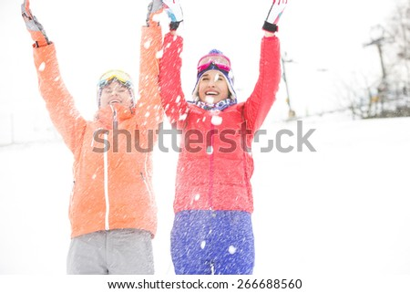 Young female friends throwing snow - stock photo