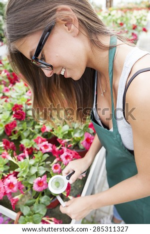 young female gardener monitors health of flowers