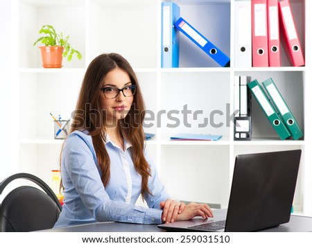 Young female general manager working at computer in her agency. Concept of new projects, ideas and success.  - stock photo