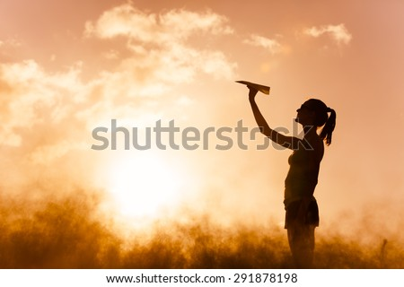 Young female getting ready to throw a paper airplane.  - stock photo