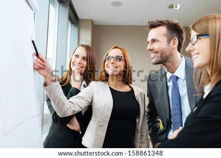 Young female giving presentation, standing at a flipchart - stock photo