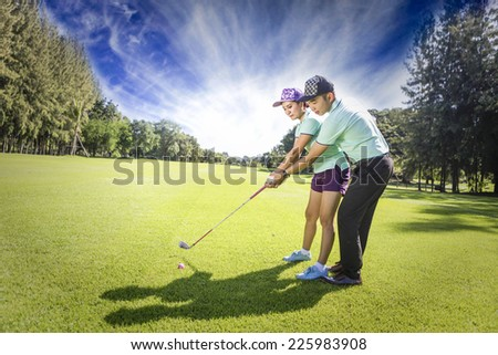 Young female golf player at Driving Range with a Golf Pro, she presumably does exercise - stock photo