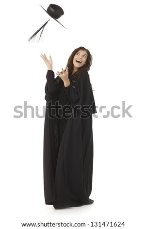 Young female graduate throwing in the air square academic cap, smiling happy. - stock photo