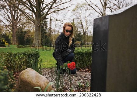 Young female grieving at cemetery. Young lady placing roses on the grave of her family member. - stock photo