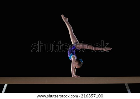 Young female gymnast performing handstand on balance beam, side view - stock photo