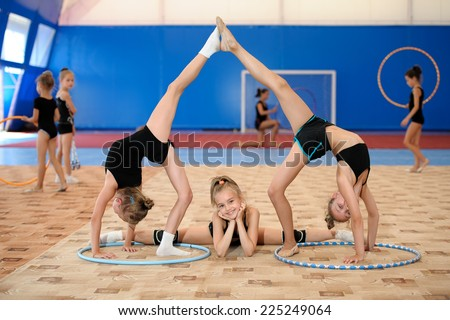 Young female gymnasts posing. Girl doing leg-split between two ones stretching legs up - stock photo