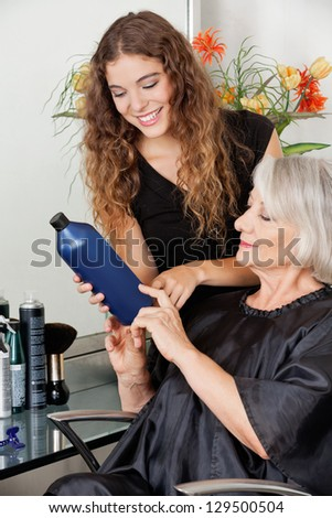 Young female hairdresser advising hair color to senior customer at parlor - stock photo
