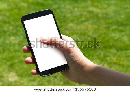 Young female hand finger touching and using smart phone with blank white screen on green background filled grass. - stock photo