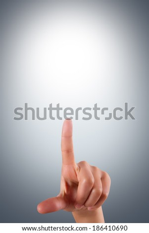 Young female hand finger touching or pressing on air screen on dark background. - stock photo