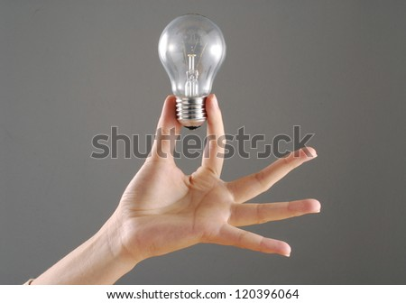Young female hand holding a bulb. - stock photo