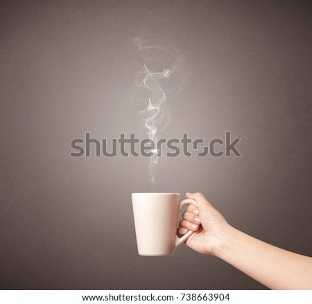 Young female hand holding steaming tea mug