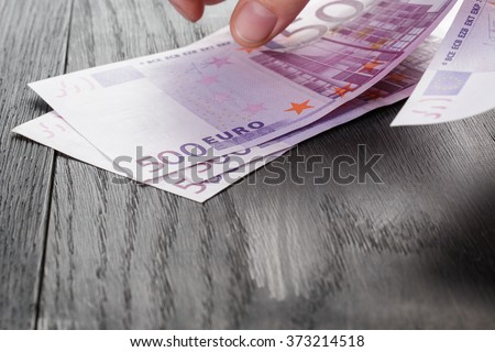 young female hands count euro bills on wood table
