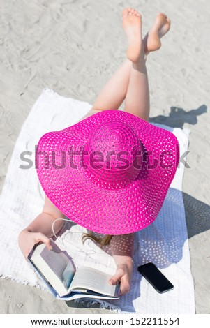 Young female hidden under big pink hat relaxing on the beach