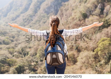 young female hiker arms open on top of mountain - stock photo