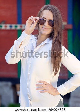 Young female hipster smiling and posing in front of a retro building, touching her glasses. Shallow depth of field. - stock photo