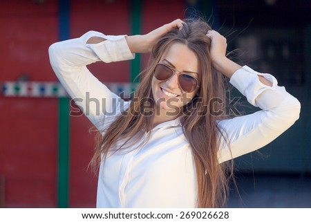 Young female hipster with glasses posing in front of a retro building, touching her hair. Shallow depth of field. - stock photo
