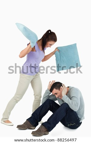 Young female hitting her boyfriend with pillows against a white background - stock photo