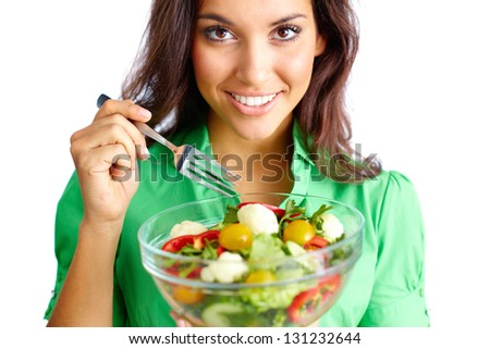 Young female holding bowl with vegetable salad and looking at camera - stock photo
