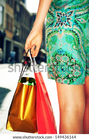Young female holding colorful shopping bags - stock photo