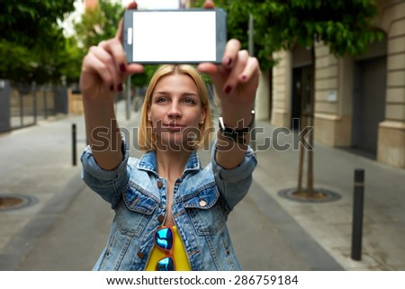 Young female holding smart phone with blank copy space area for your text message or content, tourist woman making self portrait with mobile phone digital camera during her vacation holidays in summer - stock photo