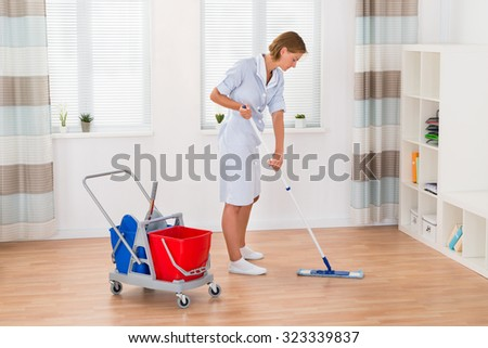 Young Female Housekeeper Cleaning Floor With Mop In House