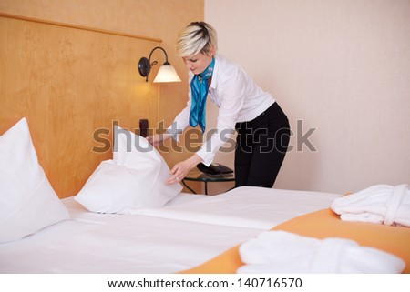 Young female housekeeper making bed in hotel room