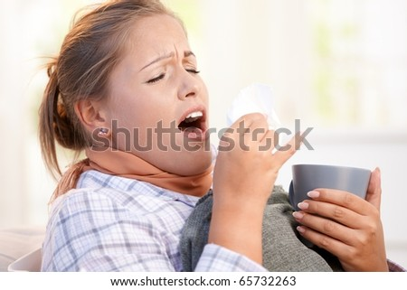 Young female in bed at home having flu, feeling bad, sneezing, drinking tea.? - stock photo