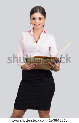 young female in business suit holding papers and folders - stock photo