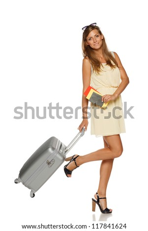Young female in elegant light dress standing with travel bag, holding passport and tickets,over white background - stock photo