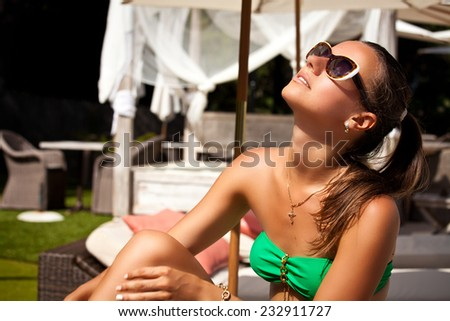 Young female in green bikini on vacation, sunbathing in hotel. Carefree summer relaxation