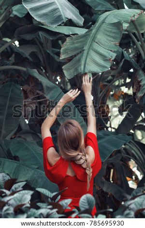 Young female in red dress and braided hairstyle standing in tropical forest near big banana leaves. Fine art photo. Conceptual