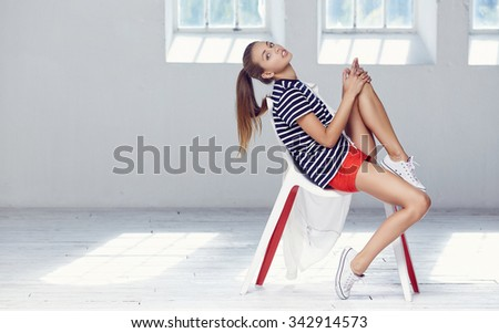 Young female in red shorts and t short sitting on chair in white room with big windows.