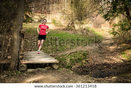 young female in skirt running on the trail over bridge in spring forest - stock photo