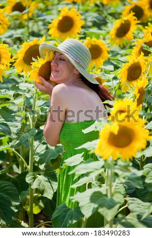 Young female in sunflower field. Her face touches a sunflower as she caressing it.