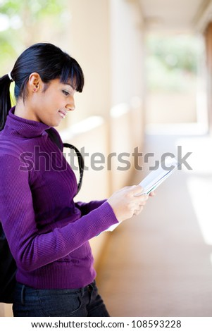 young female indian college student reading book - stock photo