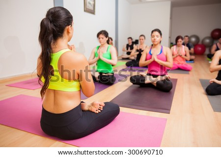 Young female instructor and her students doing some meditation during their yoga class - stock photo